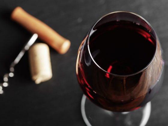 wine glass of red wine with a corkscrew.